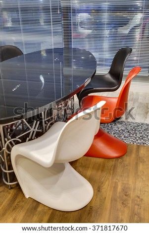 office room with a glass table and multi-colored chairs - stock photo