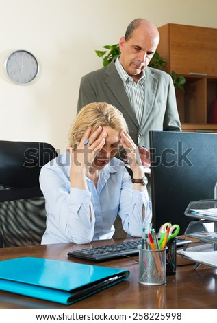 Office scene with angry aged chief and careless elderly female secretary - stock photo
