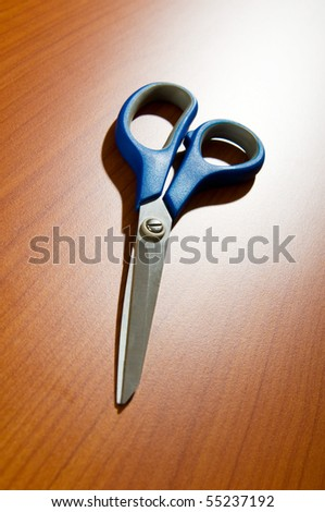 Office scissors against wooden background