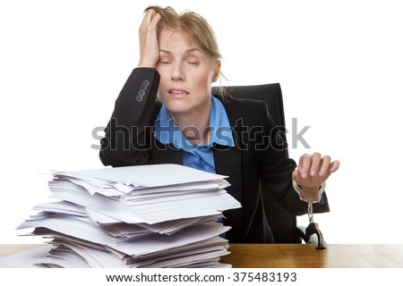 Office shot of heavy workload concept with pile of paper and woman worrying about the amount of work.  chained to desk