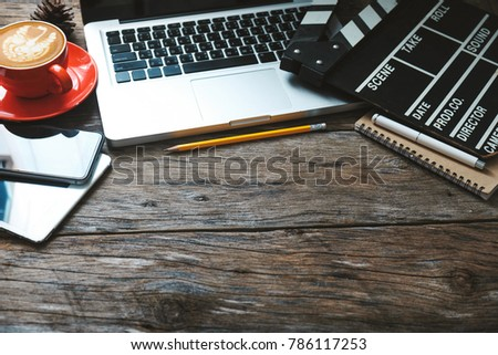 office stuff with Movie clapper laptop and coffee cup pen notepad on the wood table top view shot.