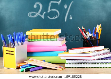 Office supplies on table on school board background  - stock photo