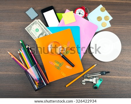 Office supplies with smartphone on wooden table - stock photo