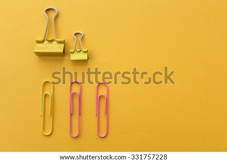 Office supply - binder clip and paper clip on yellow background - stock photo