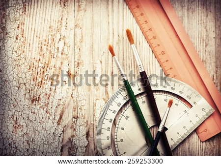 Office supply collection - brush, ruler, copybook, brushes on wooden table background. Back to school, business background - stock photo