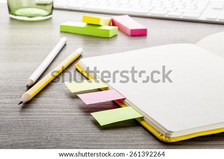 Office supply collection - notebooks, pencils, colored flags - on brown wooden table. - stock photo