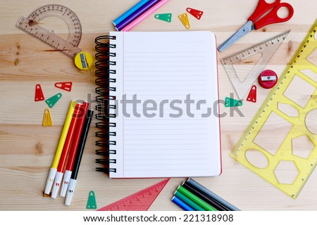Office Supply Frame on Wood Desk. Copy Space on Notepad. - stock photo