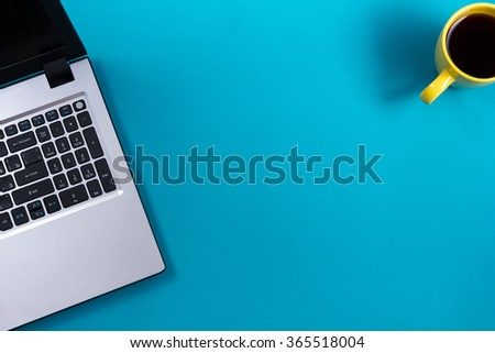 Office table desk with set of colorful supplies, white blank note pad, cup, pen, pc, crumpled paper, flower on blue background. Top view and copy space for text. - stock photo