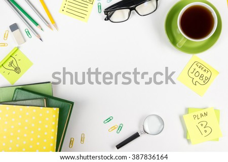 Office table desk with set of colorful supplies, white blank note pad, cup, pen, pc, crumpled paper, flower on white background. Top view and copy space for text - stock photo