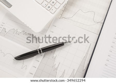 Office table with a computer, graphics, pen and notepad