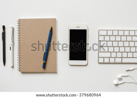 Office table with computer keyboard, notepaper, pen and smartphone. copy space - stock photo