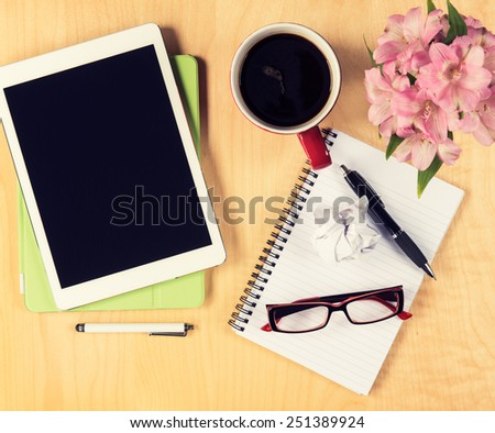 Office table with digital tablet, reading glasses cup of coffee and notepad. View from above with copy space - stock photo