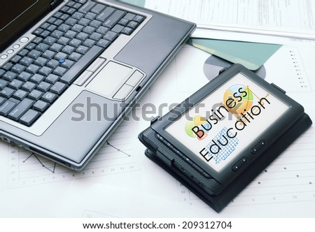 office table with electronic devices and blank sheet of paper Business education text on tablet - stock photo