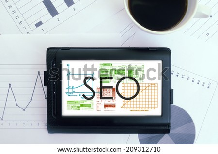 office table with electronic devices and blank sheet of paper. SEO text on tablet - stock photo