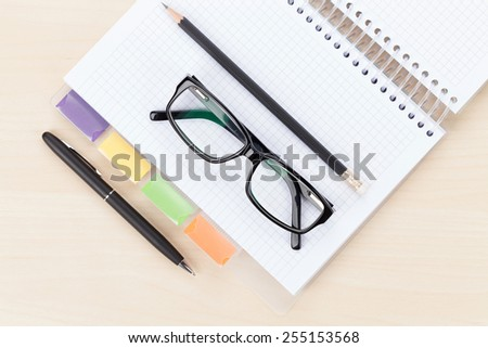 Office table with glasses over notepad, pen and pencil. Top view - stock photo