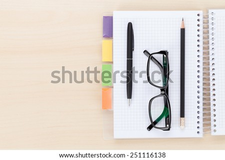 Office table with glasses over notepad, pen and pencil. Top view with copy space  - stock photo