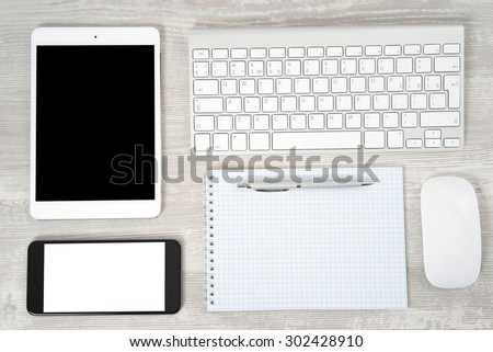 Office table with notebook, computer keyboard and mouse, tablet pc and smartphone - stock photo
