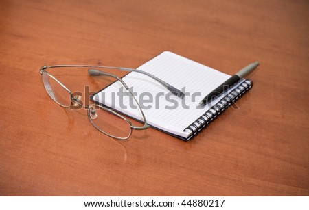 office table with notebook, pen and glasses - stock photo