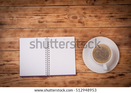 Office table with notepad and coffee cup.View from above with copy space.