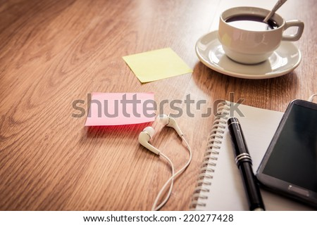 Office table with notepad,  coffee cup , pen , smartphone , headphone, sticky notes. View from above with copy space. Instant photo split toning color effect - stock photo