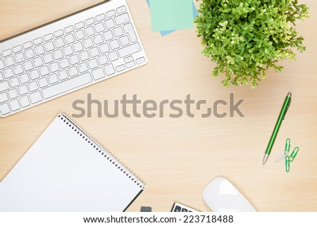 Office table with notepad, computer and flower. View from above with copy space - stock photo