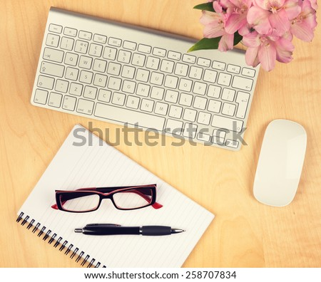 Office table with notepad, computer and reading glasses. View from above with copy space. - stock photo