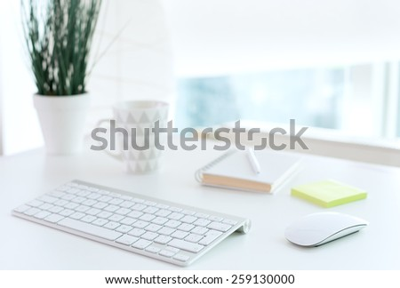 Office table with notepad, computer, flower and coffee cup - stock photo