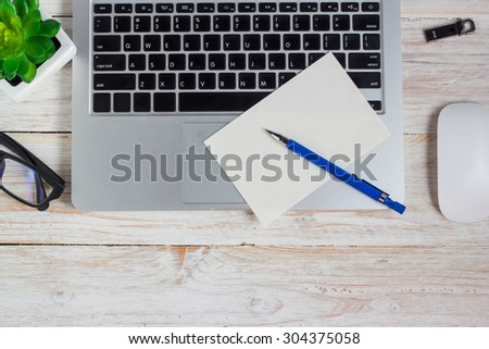 office table ,Workplace, laptop glasses and note paper on wooden table. - stock photo