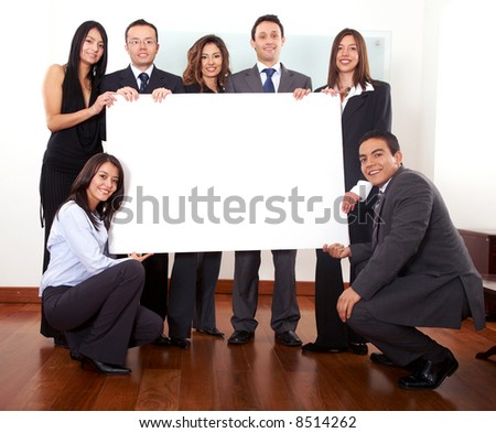 office team holding a piece of cardboard in their office - stock photo