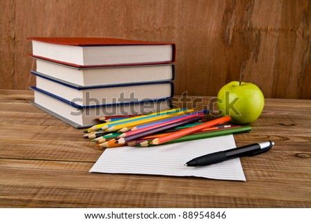 office tools and  apple on a wooden background
