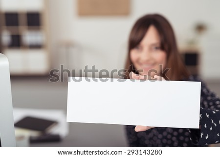 Office Woman at her Worktable Holding White Rectangular Paper with Copy Space for Texts and Showing at the Camera. - stock photo