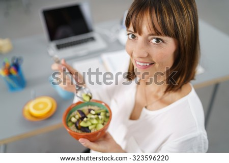 Office Woman Sitting at her Desk, Smiles at the Camera While Holding her Healthy Meal in a Bowl. - stock photo