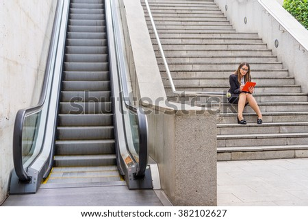 Office woman working in the stairs near scalator with tablet