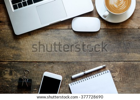 Office wood table with notepad,laptop smartphone pen mouse and coffee cup. View from above with copy space - stock photo