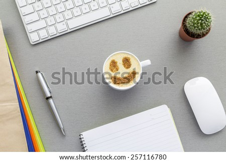 Office work space on grey desk with cactus and cappuccino. From above view on grey wooden desk with well organized office supplies and mug with cappuccino with chocolate smiley on the surface - stock photo