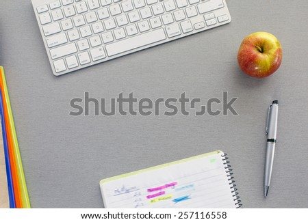 Office work space on grey desk with green apple. From above view on grey wooden desk with well organized office supplies and red apple. Notepad with hand notes marked with bright colors - stock photo