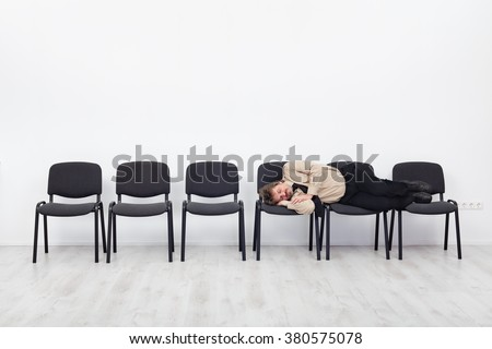 Office worker asleep on row of chairs - coping with overtime - stock photo