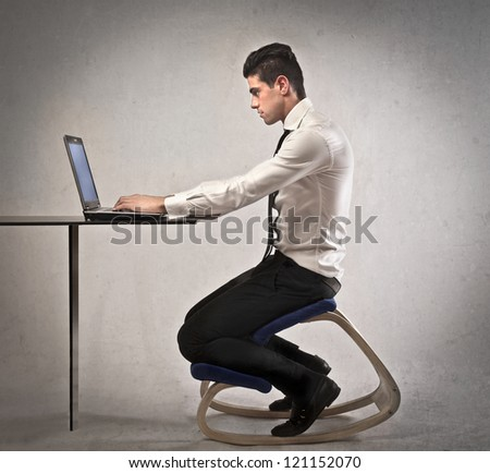 Office worker, at a desk, using a laptop computer - stock photo