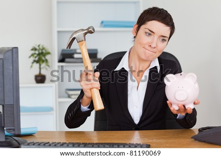 Office worker breaking a piggy bank with a hammer in her office - stock photo