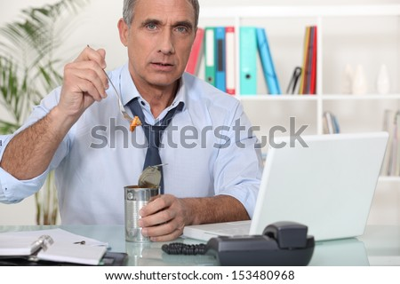 Office worker eating from tin can - stock photo