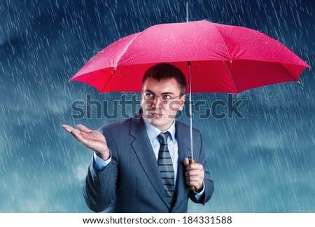 Office worker hiding under an umbrella - stock photo