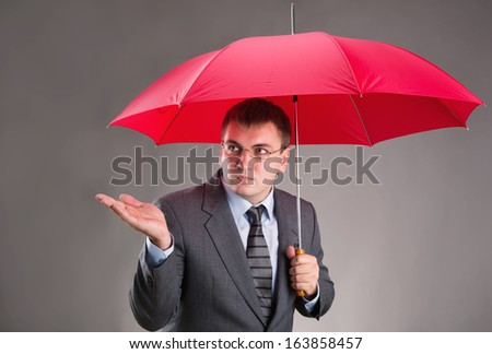 Office worker hiding under an umbrella and waiting for the rain