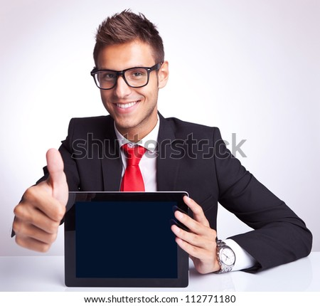 Office worker holding blank digital tablet pad and making ok hand gesture