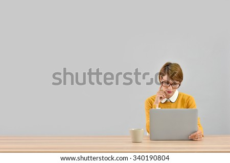 Office worker in front of laptop, grey background - stock photo