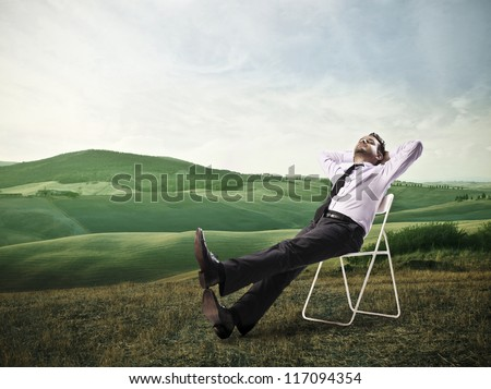 Office worker is lying on a chair in a large grace field - stock photo