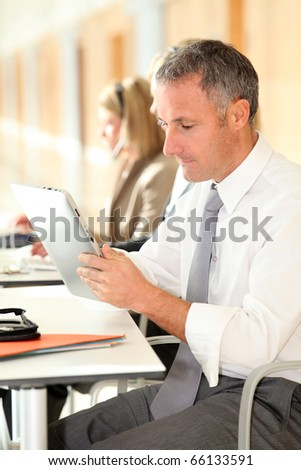 Office worker looking at internet on electronic pad - stock photo