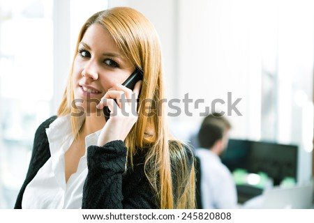 Office worker making a phone call understanding the importance of positive attitude - stock photo