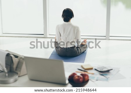 Office worker meditating on the floor, rear view - stock photo