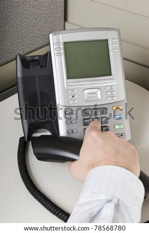 Office worker placing a call on an IP phone