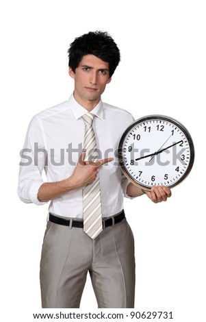 Office worker pointing his finger to a clock - stock photo